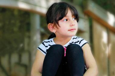 Ayan, ein kleines Flüchtlingsmädchen aus Aserbaidschan, schaut verträumt durch die Gegend.