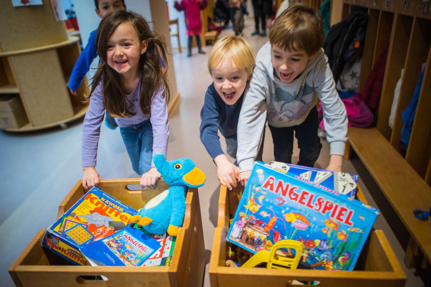 Drei Kinder schieben begeistert Spielzeugkisten durch die Kita.