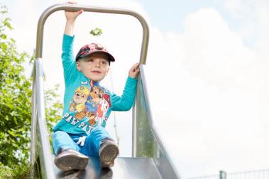 Ein Junge sitzt oben auf einer Rutsche.