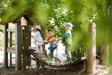 Drei Kinder spielen auf einem Klettergerüst.