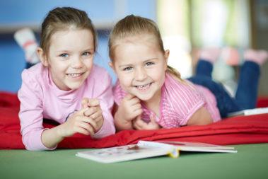 Zwei Mädchen liegen nebeneinander auf dem Bauch und lächeln in die Kamera.