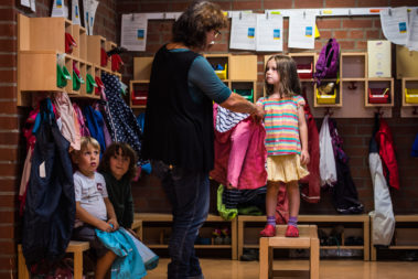 Eine Erzieherin hilft einem Mädchen beim Anziehen der Jacke.