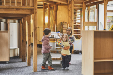 Drei Kinder schieben einen Frühstückswagen durch die Kita.