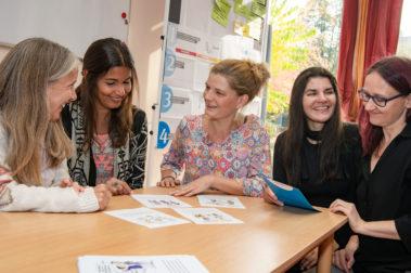 """Das Team der Kita """"Weidenkätzchen"""" in Berlin sitzt am Pädagogischen Tag zusammen und geht der Frage nach, welchen Stellenwert Sicherheit und Gesundheit in ihrer Kita haben."""