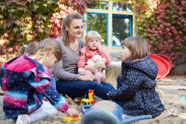 Vier Mädchen sitzen mit ihrer Erzieherin im Sand und reden miteinander.