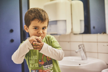 Ein kleiner Junge steht im Bad der Kita und putzt sich die Zähne.