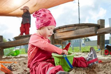 Ein kleines Mädchen sitzt unter einem Sonnensegel im Sand und spielt konzentriert mit einem Eimer und einer Schaufel..