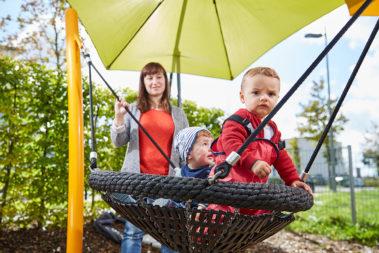 Zwei Krippenkinder schaukeln unter einem Sonnensegel und unter Aufsicht einer Erzieherin.