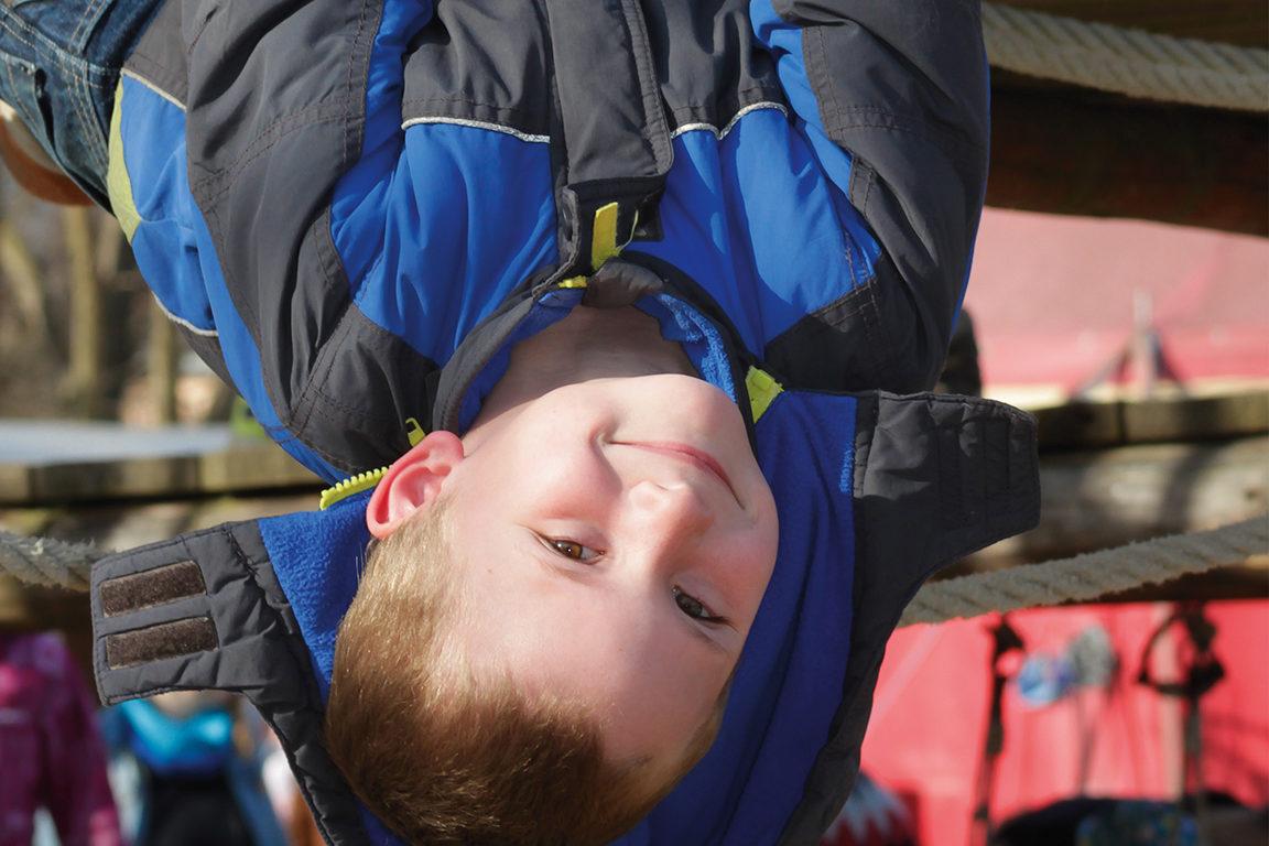 Ein Junge hängt kopfüber am Klettergerüst auf einem Spielplatz.