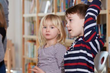 Ein Mädchen und ein Junge aus der Vorschulklasse besuchen die Grundschule und stellen Fragen.