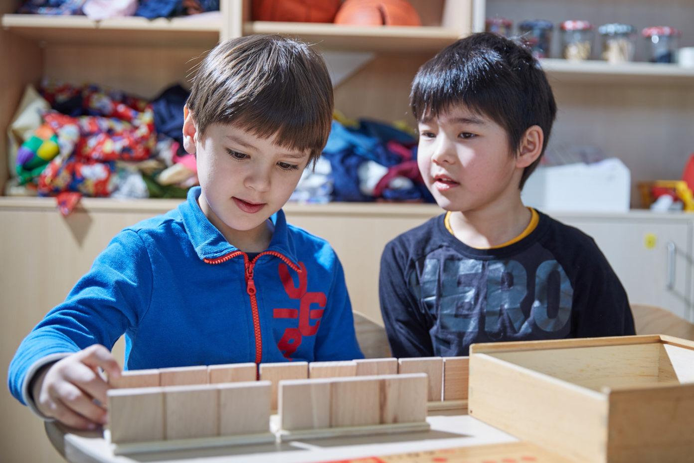 Zwei Jungs beschäftigen sich im Spielzimmer gemeinsam mit einer Kiste.