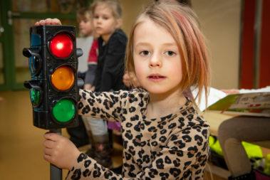 Ein Mädchen hält eine kleine Ampel in der Hand und übt damit die Verkehrsregeln.