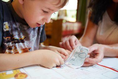 Ein Junge klebt einen zuvor aus einem Bilderbuch geschnittenen Elefanten wieder in das Buch.
