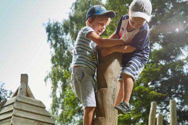 Zwei Jungen klettern an einem Kletterbaum.