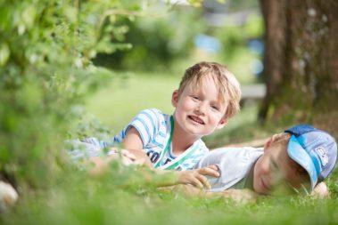Zwei Jungen liegen auf dem Kita-Gelände im Gras.