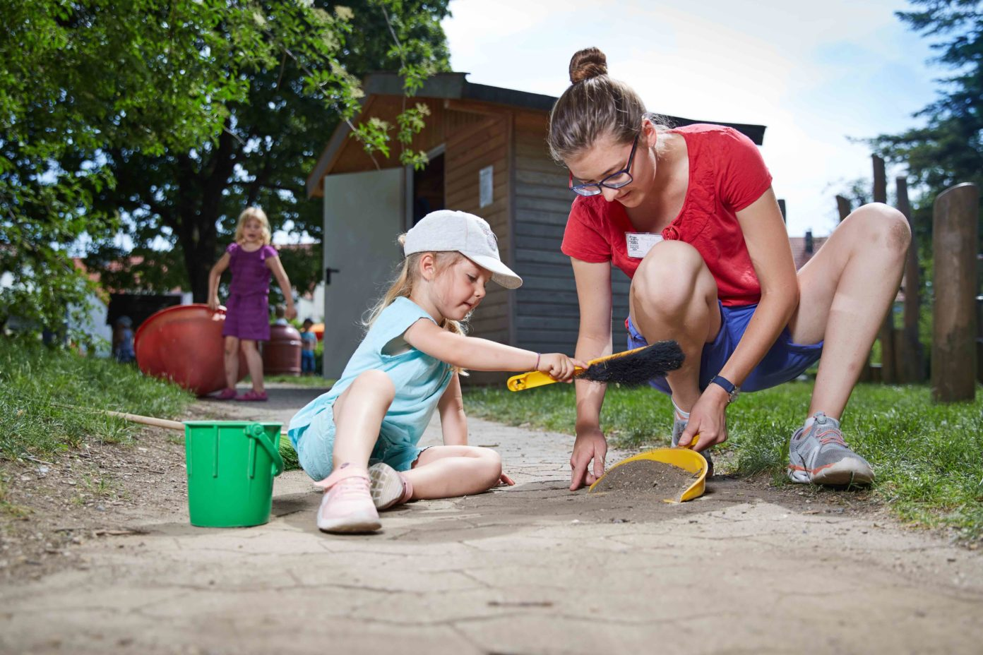 Ein kleines Mädchen hilft ihrer Erzieherin beim Fegen eines Gartenweges der Kita.
