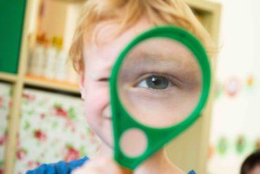 Portrait eines Kindes, das eine Lupe vors Auge hält, wodurch man das Auge im Vordergrund sehr groß sieht.