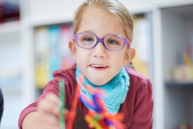 Lia sitzt an einem Tisch im Spielraum der Kita Pusteblume in Windesheim und malt. Sie ist mit einem Genfehler geboren und hat einen höheren medizinischen Unterstützungsbedarf.