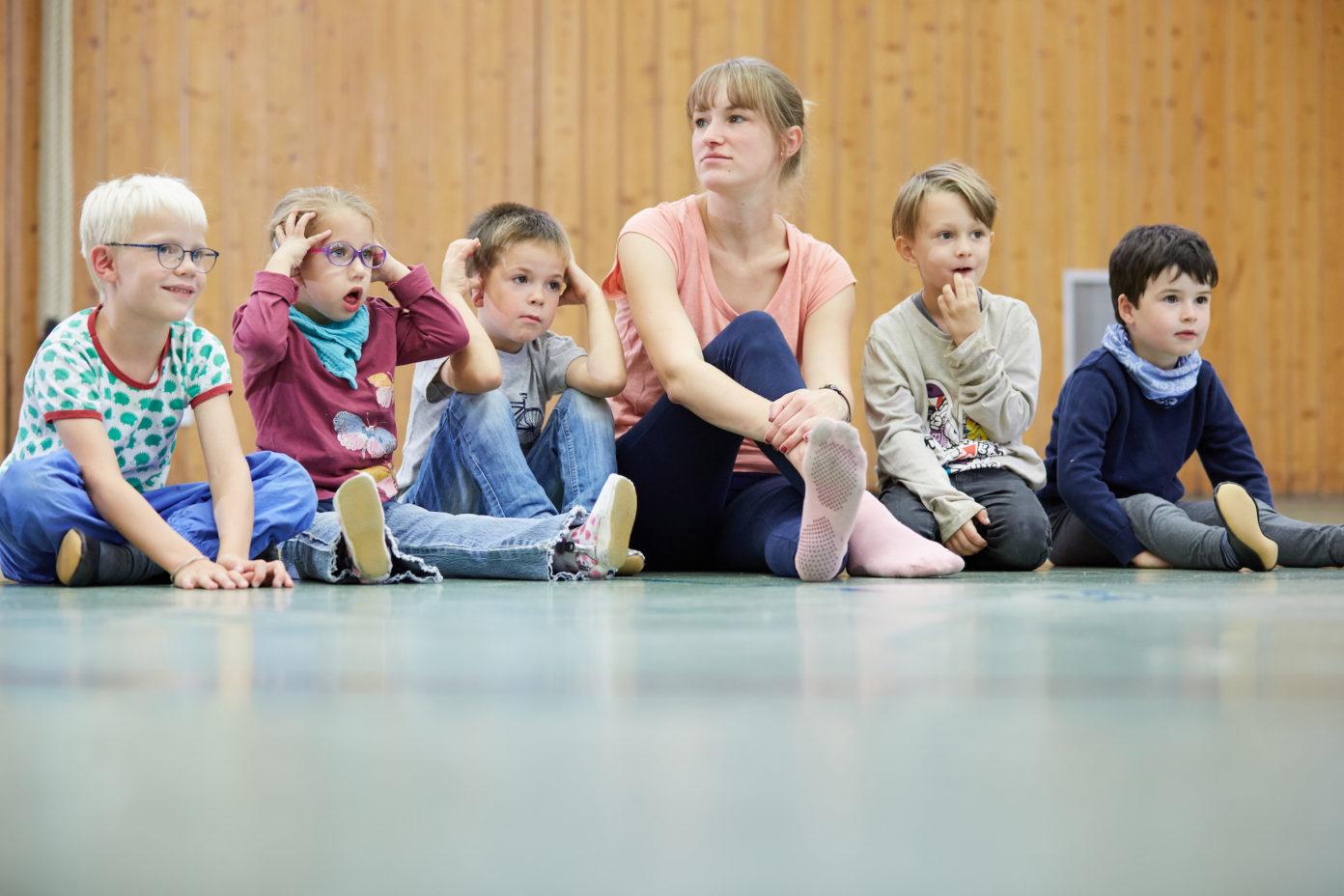 Eine Erzieherin und fünf Kinder sitzen in der Turnhalle der Kita.