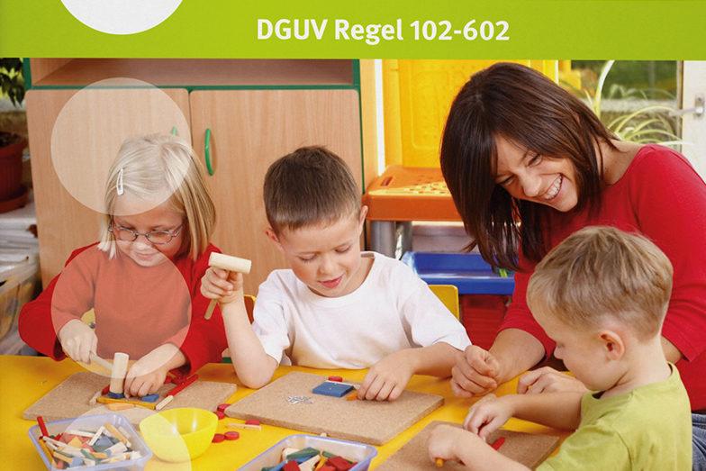 Eine Erzieherin spielt mit drei Kindern im Spielzimmer.