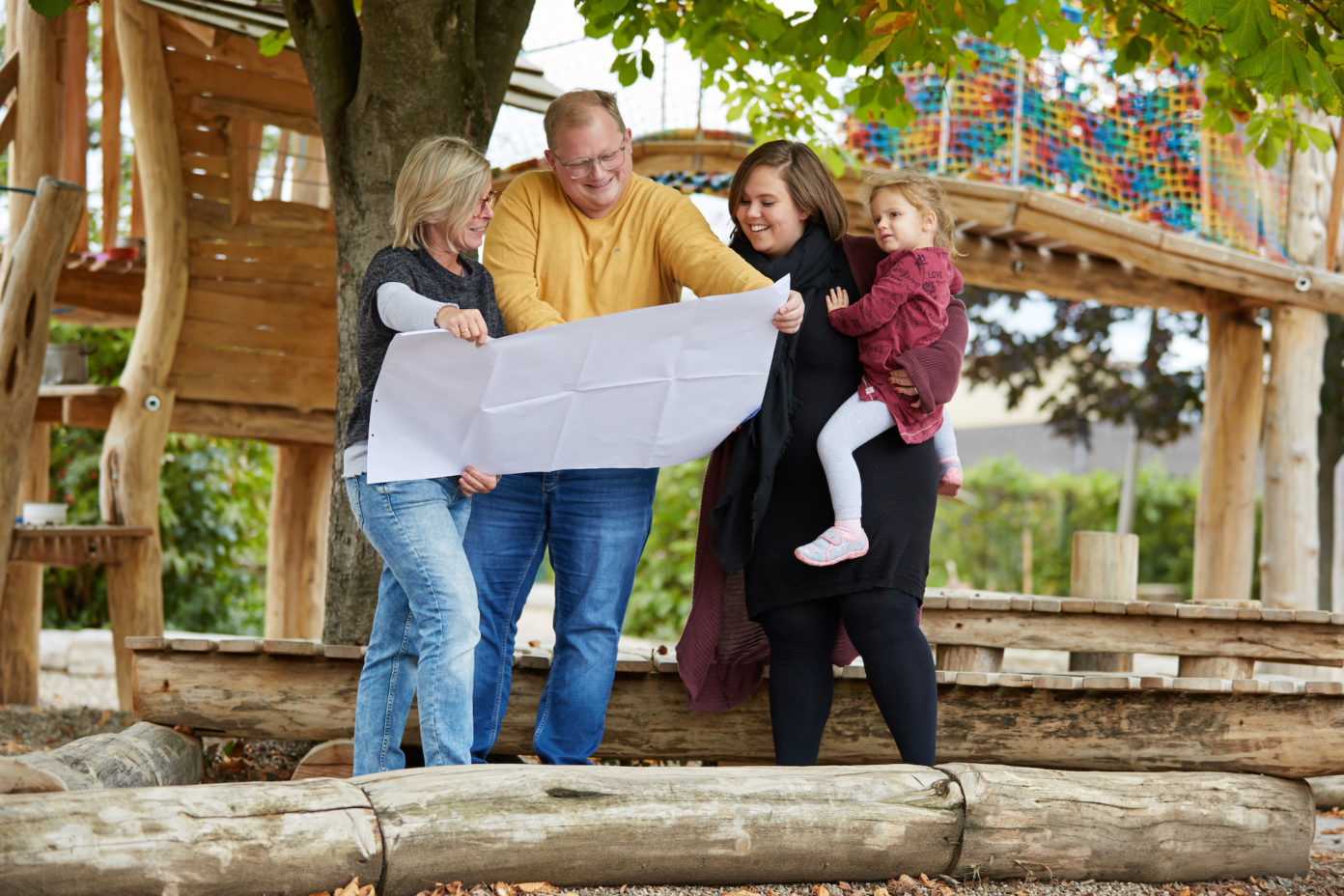 Eltern mit einem Bauplan in der Hand vor einem Klettergarten.