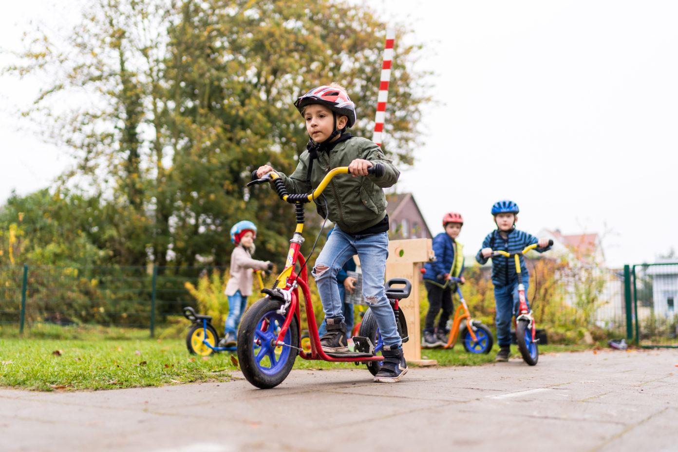 Drei Jungs und ein Mädchen fahren auf dem Weg vor ihren Häusern mit ihren Rollern.