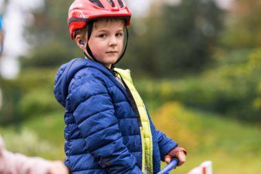 Ein Junge steht auf seinem Roller und guckt in die Kamera.