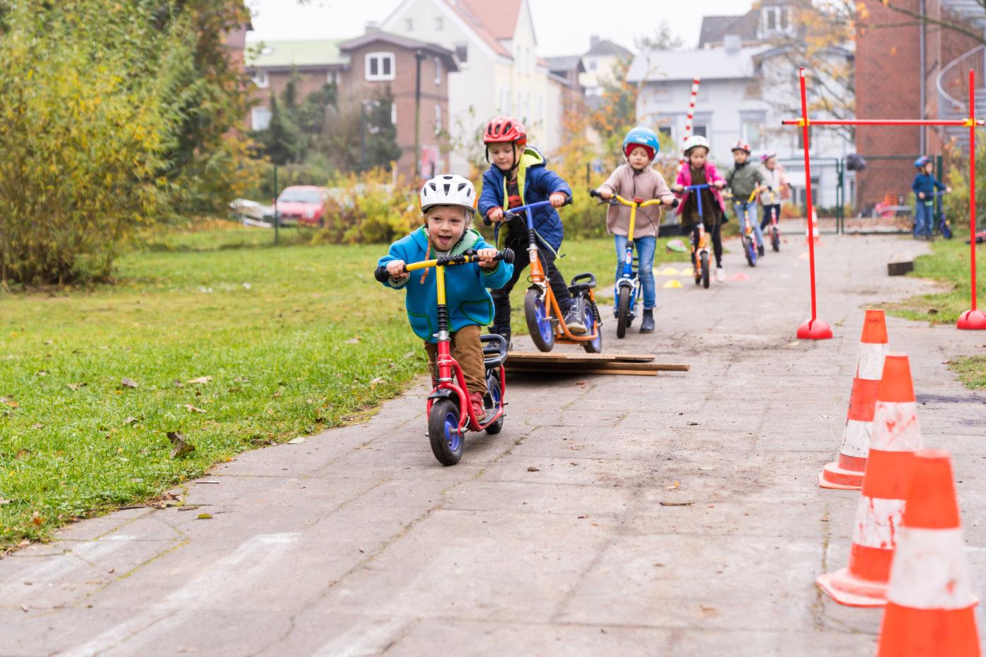 Mehrere Kinder fahren auf ihren Rollern durch einen Parcours.