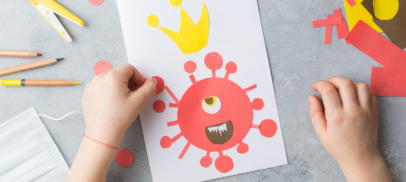 Kinderhände basteln ein Bild, das das Corona-Virus darstellt.