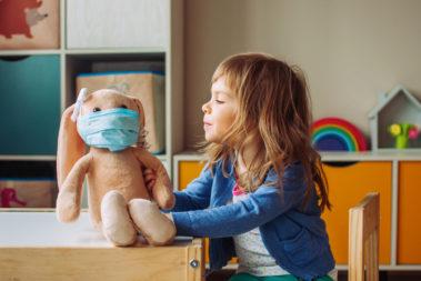 Ein kleines Mädchen spielt mit einem Stoffhasen, der eine medizinische Maske trägt. Sie sitzt an einem Tisch im Kinderraum.
