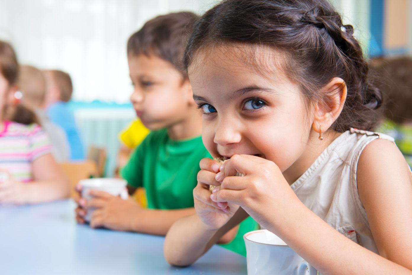 Ein kleines Mädchen sitzt an einem Kindergarten-Esstisch und isst einen Keks, der Junge neben ihr trinkt Milch.