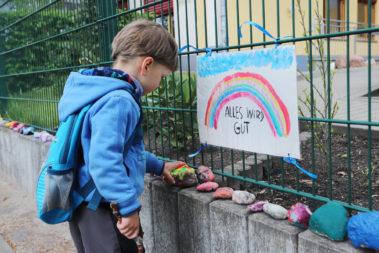 """Ein kleiner Junge legt während der Corona-Zeit am Zaun vor seinem geschlossenen Kindergarten einen bemalten Stein unter ein Plakat mit Regenbogen, auf dem steht """"Alles wird gut""""."""